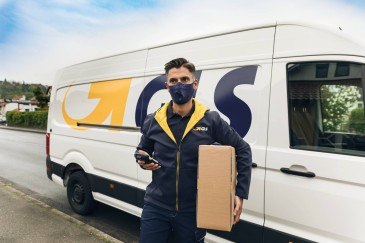 Masked driver takes parcel out of GLS delivery van