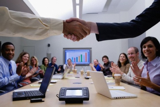 shaking hands in front of a GLS employee sitting at a conference table.