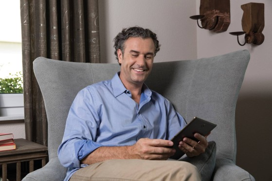 GLS customer sitting on a sofa in living room, using his smartphone